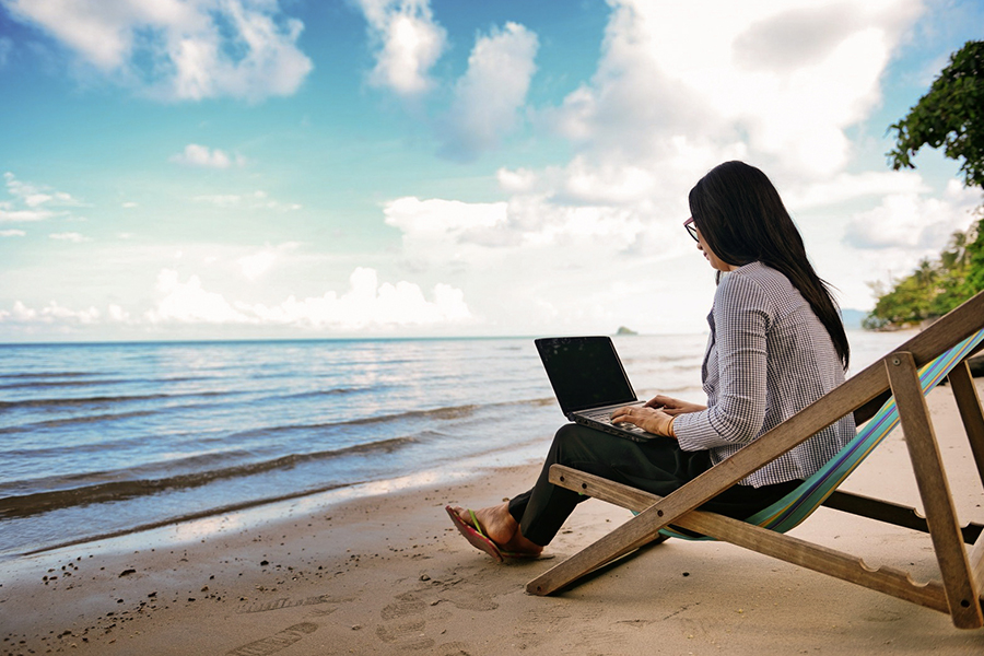 girl with a laptop on the beach